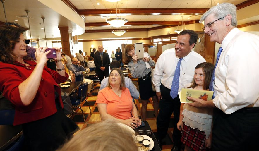 New Jersey Gov. Chris Christie, second from right, and Mississippi Gov. Phil Bryant, right, pose for a photograph with a young patron during a meet-and-greet at a restaurant in Flowood, Miss., Tuesday, May 5, 2015. Christie, in his first out-of-state trip since two former allies were indicted and a third pleaded guilty to corruption charges for their roles in the George Washington Bridge traffic scandal, is on a jaunt through Mississippi and Louisiana to raise money for fellow Republicans. (AP Photo/Rogelio V. Solis)