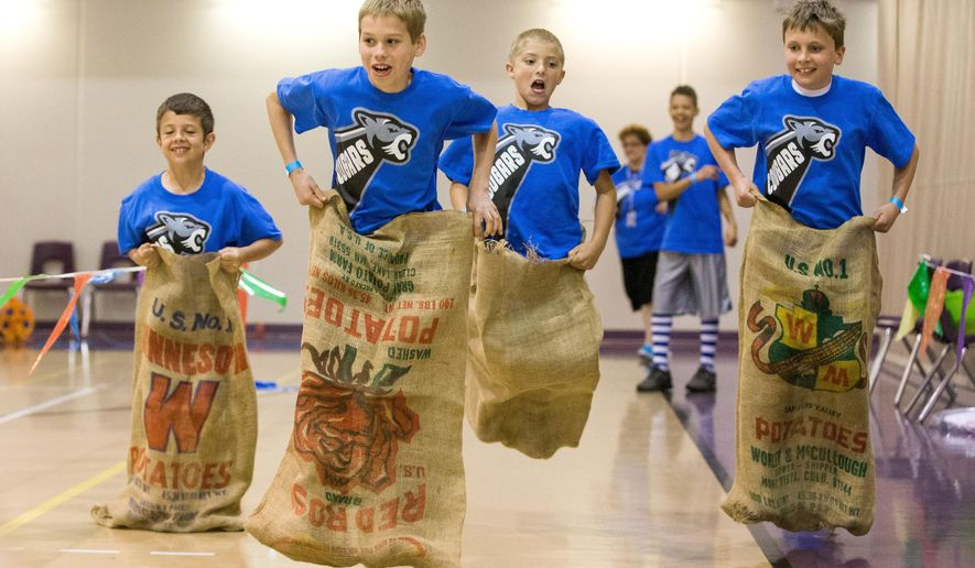In this May 1, 2015 photo, Cornerstone Christian School students, from left, Andrew Schuler, Michael Wiebelhaus, Mason Kipper, Benjamin Pfortmiller participate in a potato sack race during a carnival at the Lied Activity Center in Bellevue, Neb. The first class of seniors from the eastern Nebraska school will graduate this month. (Brendan Sullivan/The World-Herald via AP) MAGS OUT; ALL NEBRASKA LOCAL BROADCAST TELEVISION OUT