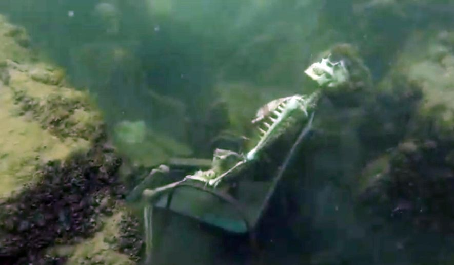 In this frame from video provided by the La Paz Sheriffs' Office, fake skeletons are strategically placed to appear as if they were sitting together with their lawn chairs bound to large rocks in the Colorado River near the Arizona and California border. A man snorkeling came across the two fake skeletons sitting in lawn chairs about 40 feet underwater and reported the skeletons to the La Paz County Sheriff's Office on Monday, May 4, 2015, launching a hunt for what authorities believed could be real bodies. (AP Photo/La Paz Sheriff's Office)