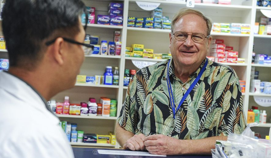 ADVANCE FOR WEEKEND EDITIONS, MAY 9-10 - In this photo taken Tuesday, May 5, 2015, Ted Lewis, right, the new CEO of Guam Seventh-day Adventist Clinic, chats with pharmacist Ken Lee at the healthcare center in Tamuning, Guam. Lewis said he's no stranger to managing struggling stateside hospitals. So when the chance came up to be the next chief executive officer for financially strapped Guam Memorial Hospital, he saw an opportunity that others might run away from.  (Rick Cruz(/The Pacific Daily via AP) MANDATORY CREDIT