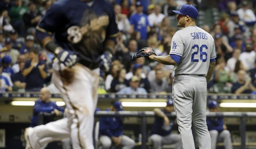 Milwaukee Brewers' Jean Segura walks to first as Los Angeles Dodgers relief pitcher Sergio Santos waits for a ball after walking in a run during the fifth inning of a baseball game Wednesday, May 6, 2015, in Milwaukee. (AP Photo/Morry Gash)