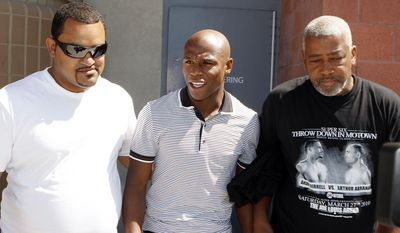FILE - In this Sept. 10, 2010, file photo, boxer Floyd Mayweather Jr., center, escorted by unidentified friends, exits the Clark County Detention Center after posting bail on a grand larceny charge stemming from a domestic violence complaint, in Las Vegas. The mother of three of Floyd Mayweather's children has sued the undefeated champion for defamation over his recent comments about a 2010 domestic violence incident in Las Vegas. Josie Harris filed the lawsuit Tuesday, May 5, 2015,  in Los Angeles, days after Mayweather defeated Manny Pacquiao in a highly anticipated bout. (AP Photo/Isaac Brekken, File)