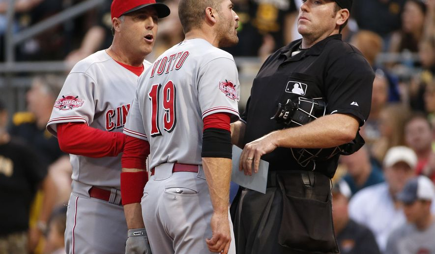 Cincinnati Reds' Joey Votto (19) bumps into umpire Chris Conroy, right, as he talks with Reds manager Bryan Price, left, during the third inning of a baseball game against the Pittsburgh Pirates, Wednesday, May 6, 2015, in Pittsburgh. Votto was ejected from the game. (AP Photo/Gene J. Puskar)