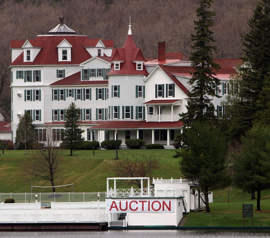 FILE - In this May 10, 2012, file photo, a large sign hangs in front of the Balsams Hotel in Dixeville Notch, N.H., where an auction was scheduled to clear out the nearly 150-year-old resort. A bill to pave the way for an ambitious plan to restore the resort got the go-ahead from New Hampshire's House of Representatives Wednesday, May 6, 2015. The bill would create a special taxing district allowing the state to back $28 million in bonds toward redeveloping the Balsams, which closed in 2011. (AP Photo/Jim Cole, File)