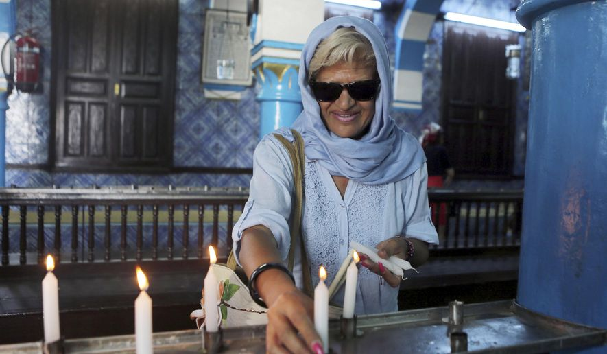 Tunisian Jew Chantal Dabi lights a candle at the Ghriba synagogue in Djerba, south Tunisia, Wednesday, May 6, 2015.  Pilgrims arrived for the pilgrimage at Tunisia's Ghriba synagogue, the oldest in Africa.  On April 11, 2002 a deadly attack on the synagogue killed 21 people, including 14 German tourists. (AP Photo/Mohsen May)