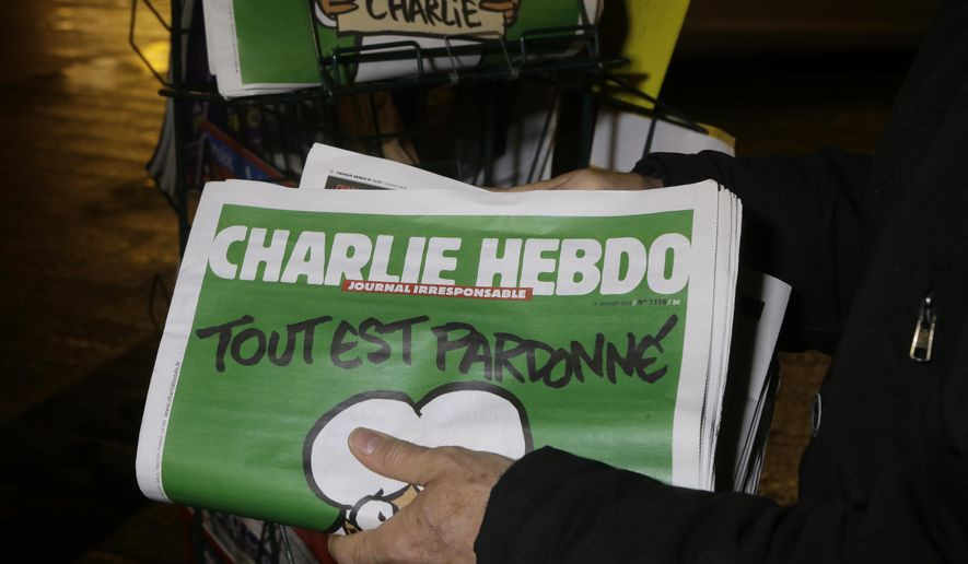A seller of newspapers stocks several Charlie Hebdo newspapers at a newsstand in Nice, France, FILE - Jan. 14, 2015. (AP Photo/ Lionel Cironneau, File) ** FILE **