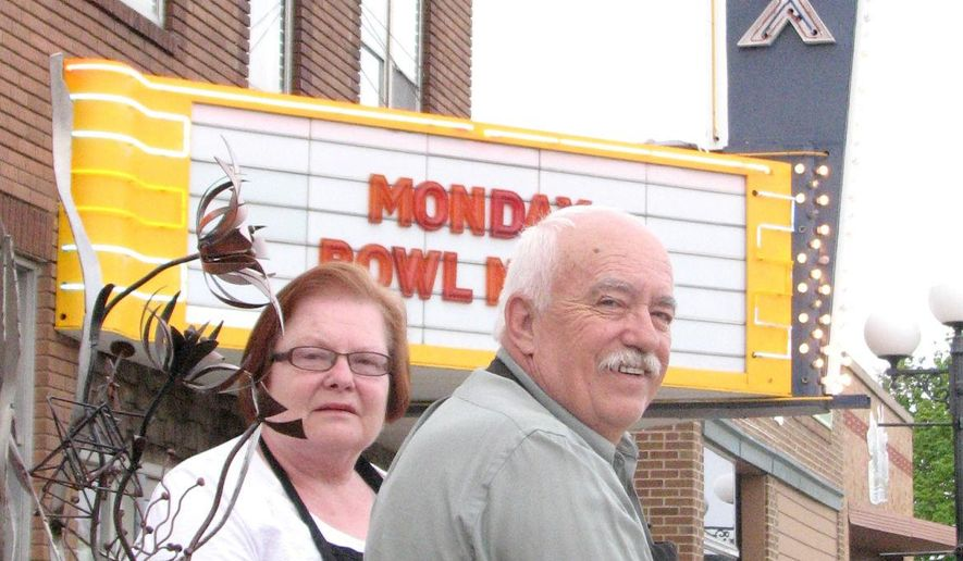 In this photo taken Monday, May 4, 2015, Aileen and Larry Pedley pose outside the Max Theater in downtown Sibley, Iowa. The couple has worked at the theater since 1962 and they bought the business in 1981. They are looking to sell the business as they look toward retirement. (Tim Gallagher/The Sioux City Journal via AP) NO SALES, MAGS OUT, TV OUT, MANDATORY CREDIT