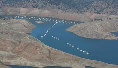 In this aerial photo taken Tuesday, April 28, 2015, house boats sit in the receding waters of Lake McClure in Mariposa County Northeast of Merced, Calif. The State Water Resources Control Board is considering sweeping mandatory emergency regulations to protect water supplies as water levels as some of California's lakes and reservoirs continue to decline. (AP Photo/Rich Pedroncelli)