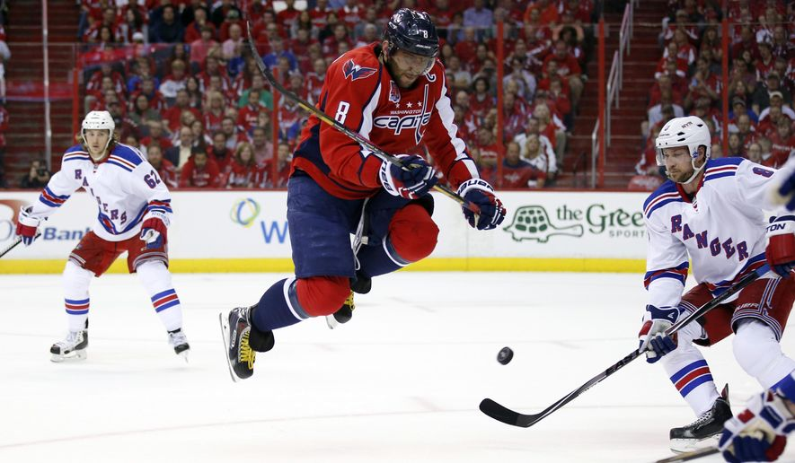 Washington Capitals left wing Alex Ovechkin (8), from Russia, jumps over a teammate's shot as New York Rangers defenseman Kevin Klein, right, defends during the first period of Game 4 in the second round of the NHL Stanley Cup hockey playoffs, Wednesday, May 6, 2015, in Washington. (AP Photo/Alex Brandon)
