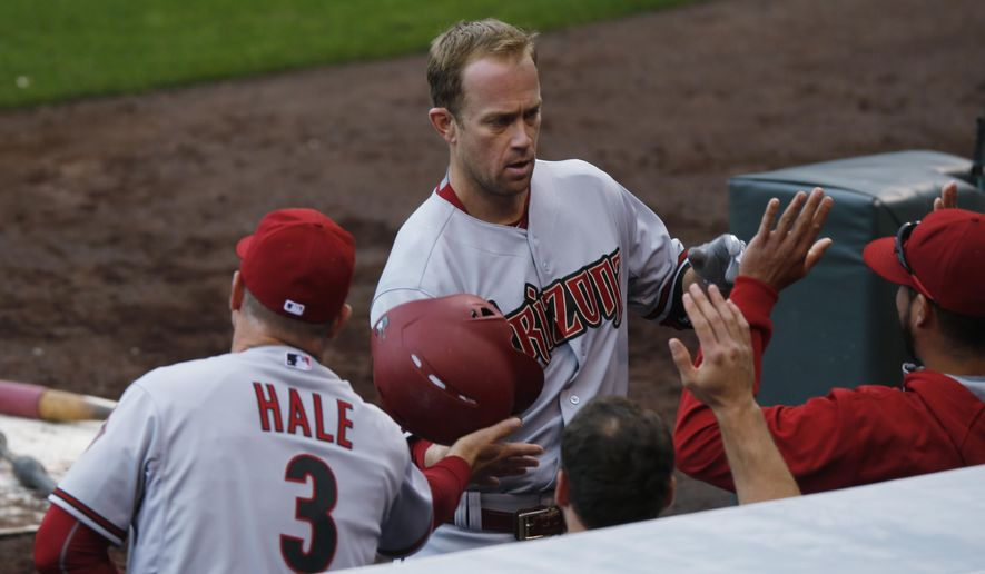 Arizona Diamondbacks manager Chip Hale, left, congratulates Arizona Diamondbacks third baseman Aaron Hill as he returns to the dugout after hitting a three-run home run against the Colorado Rockies in the fourth inning of the first game of a baseball doubleheader Wednesday, May 6, 2015, in Denver. (AP Photo/David Zalubowski)