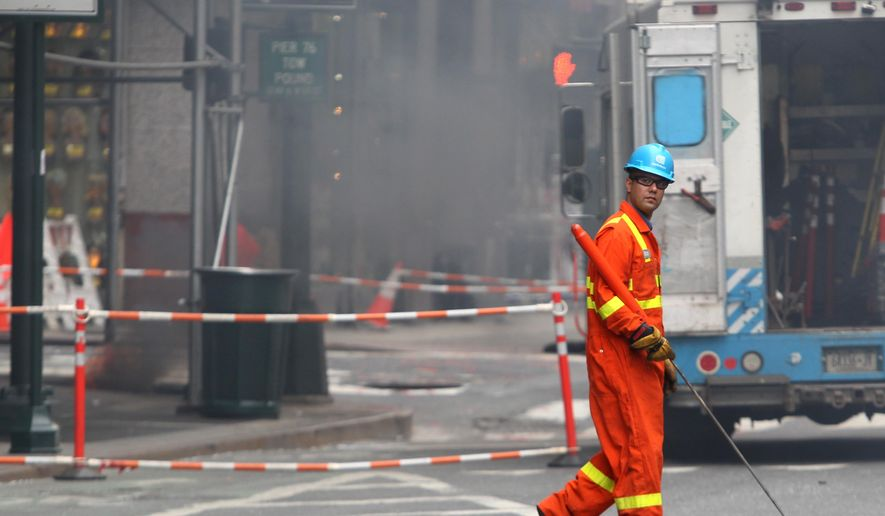 A utility worker passes a fire, at left, burning in a manhole in New York on Wednesday, May 6, 2015. An explosion in the manhole near Penn Station in midtown Manhattan snarled traffic in the area. Fire officials say there were no injuries. (AP Photo/Peter Morgan)