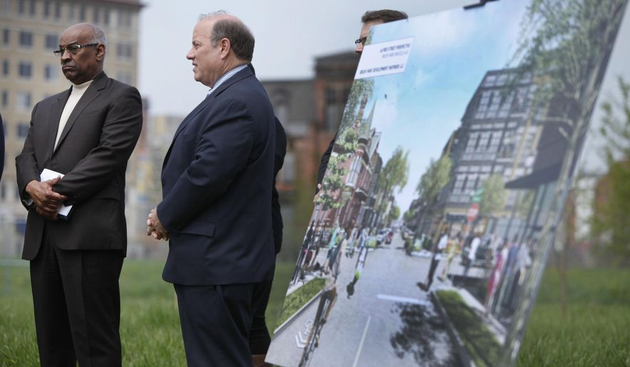 Charlie Beckham and Detroit Mayor Mike Duggan stand next to a rendering of a proposed development during news conference to announce the development partnership that will transform about eight acres in Brush Park, Wednesday, May 6, 2015, in Detroit. About 300 new residential units are planned as part of the $70 million development in the neighborhood just north of downtown Detroit. (Diane Weiss/Detroit Free Press via AP)  DETROIT NEWS OUT; TV OUT; MAGS OUT; NO SALES; MANDATORY CREDIT DETROIT FREE PRESSSS