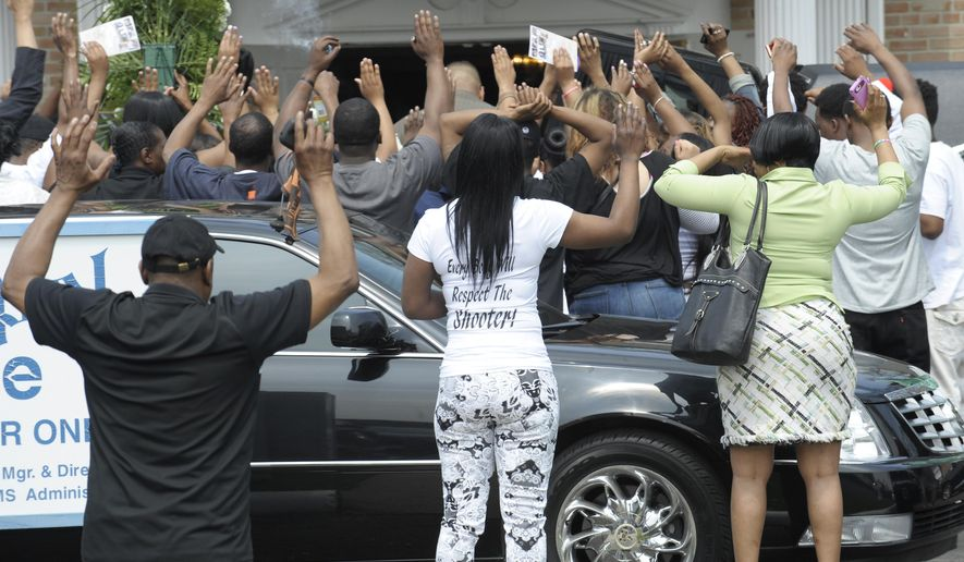 Mourners raise their hands to block the media from seeing the casket of Terrance Kellom at the end of the service at the Trinity Chapel Funeral Home in Detroit, Wednesday, May 6, 2015. Kellom was shot multiple times on April 27 by a member of a regional fugitive task force that was seeking him. (Clarence Tabb Jr./The Detroit News via AP)