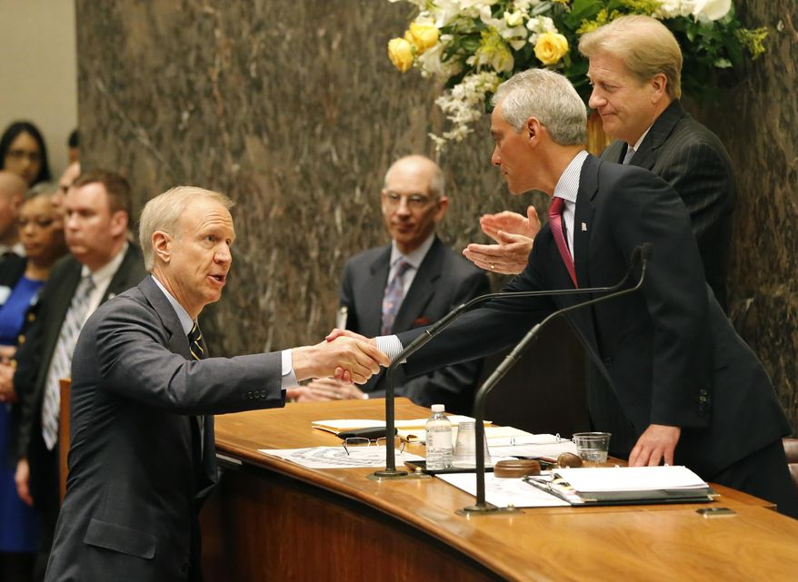 Illinois Gov. Bruce Rauner, left, shakes the hand of Chicago Mayor Rahm Emanuel, right, before Rauner's address to the city council Wednesday, May 6, 2015, in Chicago. The historic address, the first by a sitting governor in the council's chambers, focused on the city's and state's financial and economic challenges. (AP Photo/Charles Rex Arbogast)