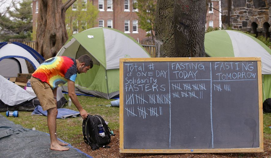 In this photo taken Tuesday, May 5, 2015, Tufts University student Jesse Mahler straighten-ups a small tented campsite next to school's administration building where students have been protesting the university's plans to cut about 35 janitorial jobs in Medford, Mass. Five students at the university began a hunger strike on Sunday in solidarity with the janitors. (AP Photo/Stephan Savoia)