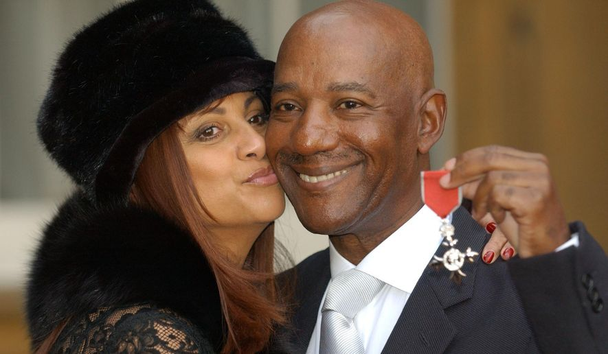 FILE - In this Nov, 27, 2003 file photo, singer Errol Brown poses with his wife Ginette after receiving an MBE, for  his services to pop music as the Hot Chocolate frontman. The singer has died in the Bahamas aged 71, his manager said on Wednesday, May, 6, 2015. (Fiona Hanson/PA Via AP, File) UNITED KINGDOM OUT .