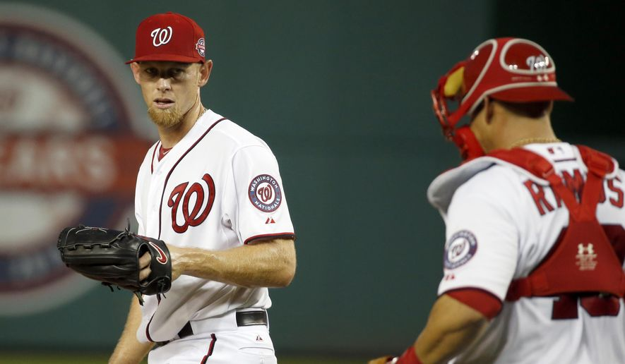 Washington Nationals starting pitcher Stephen Strasburg, left, looks at catcher Wilson Ramos during the second inning of a baseball game against the Miami Marlins at Nationals Park, Tuesday, May 5, 2015, in Washington. Strasburg was relieved in the third inning. (AP Photo/Alex Brandon)