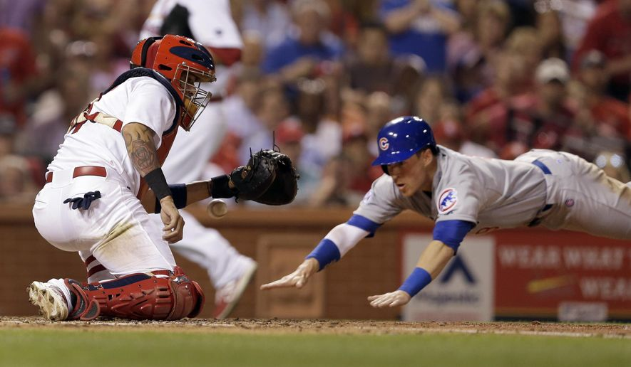 Chicago Cubs' Chris Coghlan, right, scores as the throw gets away from St. Louis Cardinals catcher Yadier Molina during the fifth inning of a baseball game Wednesday, May 6, 2015, in St. Louis. (AP Photo/Jeff Roberson)