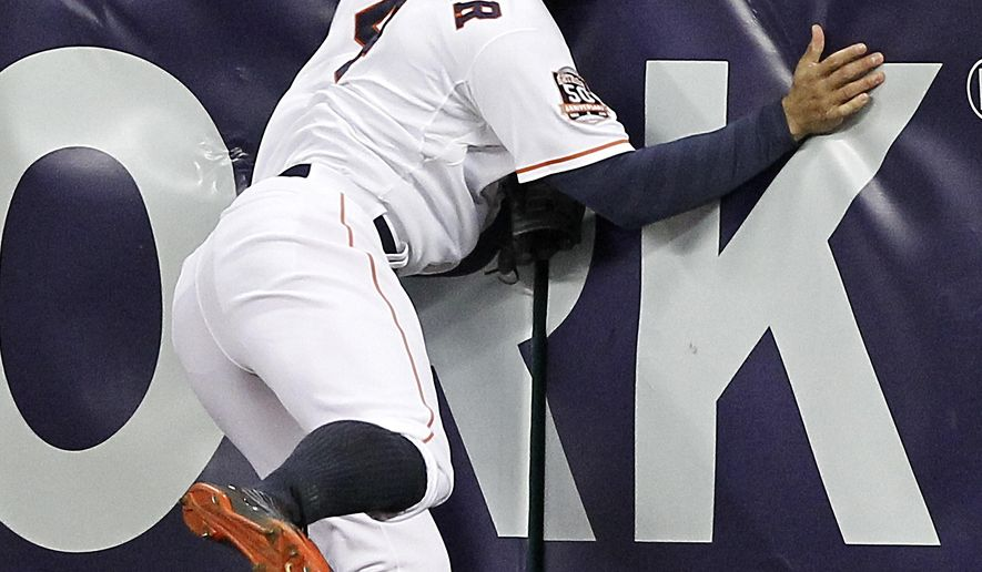 Houston Astros right fielder George Springer (4) slams into the wall makeing a running catch on a fly ball hit Texas Rangers'  Adrian Beltre in the seventh inning in a baseball game Tuesday May 5, 2015, in Houston. (AP Photo/Bob Levey)