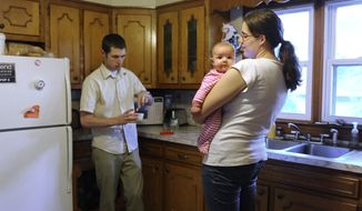 "In this Monday, Sept. 19, 2011 photo, Rebecca Allred, a second-year chemistry doctoral student at Yale, holds daughter Anna as her husband, Jacob, prepares dinner at home in New Haven, Conn. With two-thirds of all undergraduate degrees and 60 percent of master's degrees now going to women, many believe it's only a matter of time before that trend influences the upper echelons of the ""STEM"" fields - science, technology, engineering and math. (AP Photo/Jessica Hill)"