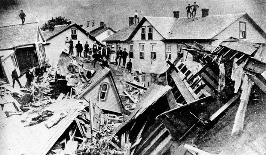 In this 1889 file photograph, people stand atop houses among ruins after disastrous flooding in Johnstown, Pa. Facts, figures and anecdotes about the Johnstown flood in Pennsylvania, which killed 2,209 people 125 years ago, gave the Red Cross its first international response effort and helped set a precedent for American liability law. (AP Photo/File)