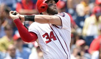 Washington Nationals right fielder Bryce Harper (34) watches the ball after hitting a second home run against the Miami Marlins during the third inning of their baseball game at Nationals Park in Washington, Wednesday, May 6, 2015. (AP Photo/Susan Walsh)
