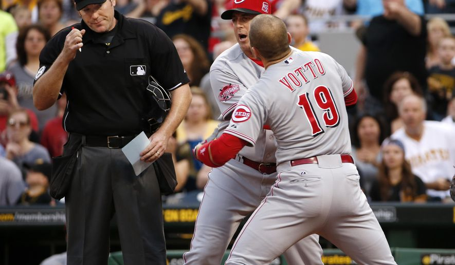 Cincinnati Reds' Joey Votto (19) is restrained from umpire Chris Conroy, left, by Reds manager Bryan Price, center, after Votto bumped Conroy in an altercation during the third inning of a baseball game against the Pittsburgh Pirates, Wednesday, May 6, 2015, in Pittsburgh. Votto was ejected from the game. (AP Photo/Gene J. Puskar)