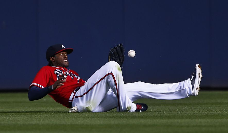 Atlanta Braves center fielder Cameron Maybin can't hang on to a ball hit for a double by Philadelphia Phillies' Ben Revere in the fifth inning of a baseball game Wednesday, May 6, 2015, in Atlanta. (AP Photo/John Bazemore)
