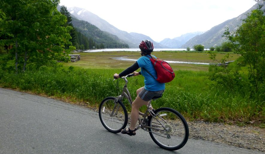 ADVANCE FOR WEEKEND EDITIONS, MAY 9-10 - In this photo taken May 26, 2014, Deb Hansen pedals a rental bike along the road out of Stehekin, Wash., after backpacking the Lake Chelan Lakeshore Trail.  Stehekin is a Northwest classic backcountry destination at the end of Lake Chelan, accessible by boat and floatplane and, most deliciously, by foot. (Rich Landers/The Spokesman Review via AP)