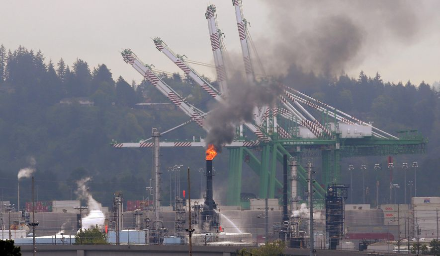 A fire burns at a U.S. Oil and Refining Co. facility Wednesday, May 6, 2015 in Tacoma, Wash. The Tacoma Fire Department says that no injuries or evacuations have been reported and that crude oil in the smokestack was burning off.  (AP Photo/Ted S. Warren)