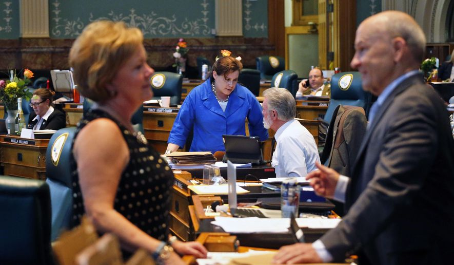 Colorado State Rep. Lori Saine, R-Firestone, second from left, talks with Rep. Jim Wilson, R-Salida, while in the foreground Rep. Polly Lawrence, R-Littleton, talks with Rep. Dan Thurlow,-R-Grand Junction, on the closing day of the 2015 Colorado legislative session, at the Capitol, in Denver, Wednesday May 6, 2015. Colorado lawmakers began the final mad dash to end of the legislative session Wednesday with plenty of major proposals pending in a divided Legislature, where Republicans run the Senate and Democrats control the House. (AP Photo/Brennan Linsley)
