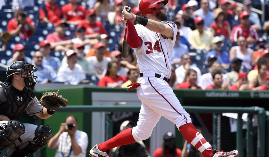 Washington Nationals right fielder Bryce Harper (34) watches the ball after hitting a home run as Miami Marlins catcher J.T. Realmuto, left, watches during the second inning of their baseball game at Nationals Park in Washington, Wednesday, May 6, 2015. (AP Photo/Susan Walsh)