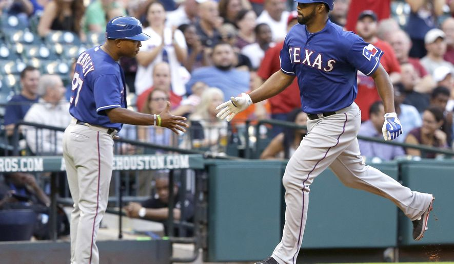 Texas Rangers' Carlos Peguero, right, is congratulated by third base coach Tony Beasley as he rounds the bases on a solo homer against the Houston Astros during the second inning of a baseball game Wednesday, May 6, 2015, in Houston. (AP Photo/Pat Sullivan)