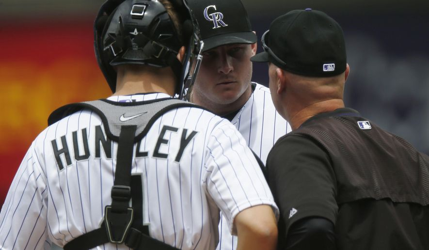 Colorado Rockies catcher Nick Hundley,  front left, confers with starting pitcher Tyler Matzek, center, and pitching coach Steve Foster after Matzek walked the bases loaded against the Arizona Diamondbacks in the first inning of the first game of a baseball doubleheader Wednesday, May 6, 2015, in Denver. (AP Photo/David Zalubowski)