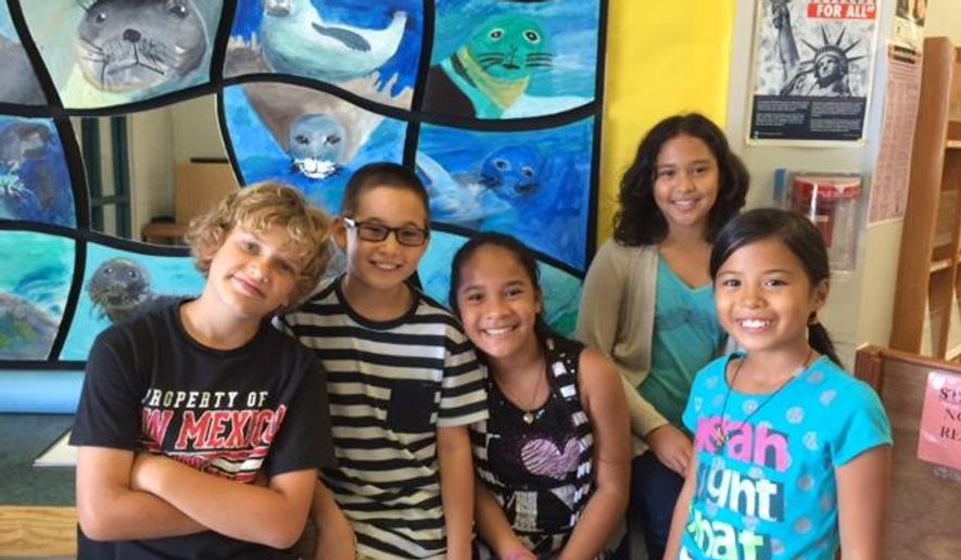 ADVANCE FOR USE SUNDAY, MAY 10, 2015, AND THEREAFTER- In this April 2015 photo, Kahakai Elementary School fourth graders Peyton Winkel, Andrey Sawinski, Lina Amor, Brooke Aragon and Taylor Bear pose for a photo in front of hand-painted mural of the monk seals at the school in Kailua-Kona, Hawaii. The young scholars spent more than two months crafting the drawings of the endangered species and joyfully expressed their knowledge and pride of the animal and a mural that has taken on a life of its own, West Hawaii Today reported. (Megan Moseley/West Hawaii Today via AP)