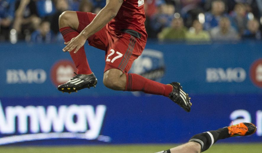 Toronto FC forward Luke Moore leaps over Montreal Impact goalkeeper Eric Kronberg during second half Amway Canadian soccer championship semifinal action Wednesday, May 6, 2015, in Montreal. The Imapct won 1-0. (Paul Chiasson/The Canadian Press via AP) MANDATORY CREDIT