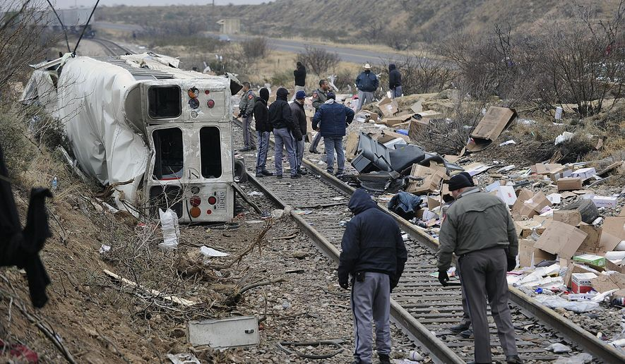 File - In this Jan. 14, 2015, file photo, authorities investigate the scene of a prison bus crash in Penwell, Texas. Jason Self is thankful to be alive after the Jan. 14 bus-train collision left him critically injured. Self, a correctional officer for the Texas Department of Criminal Justice, said he has no memories of the crash, which occurred when a prison bus taking inmates from the Middleton Unit in Abilene to Sanchez State Jail in El Paso skidded off an icy road near Odessa and slid down an embankment into the path of an oncoming freight train. (Mark Sterkel/Odessa American via AP, File)