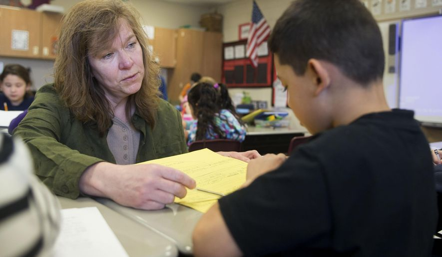 In this March 26, 2015 photo, second-grade bilingual teacher Beth Limones works with Jayson Sepulveda at Seth Whitman Elementary School in Belvidere, Ill. Belvidere Superintendent Michael Houselog estimated that 1,200 of the district's 8,000 students are Spanish-speakers. Implementing dual-language programs in the schools is one way the district is adapting. (Max Gersh/Rockford Register Star via AP) MANDATORY CREDIT