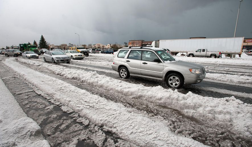Vehicles drive through the deep hail and water along North Academy Boulevard after a hail storm Thursday, May 7, 2015, in Colorado Springs, Colo. A storm system sweeping across the state brought heavy rain to much of Colorado's Front Range, including up to 8 inches of hail in Colorado Springs. (Christian Murdock/The Gazette via AP) MAGS OUT; MANDATORY CREDIT