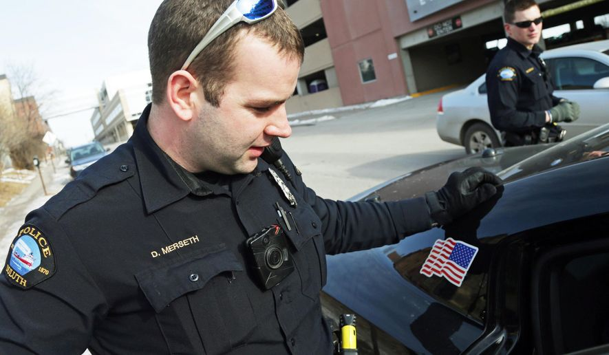 FILE - In this Feb. 2, 2015 file photo, Duluth police officer Dan Merseth, left, wear a the body camera on the front of his uniform during his shift in Duluth, Minn. Cleveland's move to buy 1,500 police body cameras and data storage could cost up to $3.3 million over five years, a higher price tag than previously known and an illustration of the long-term costs of such programs with Taser International. (AP Photo/Jim Mone, File)