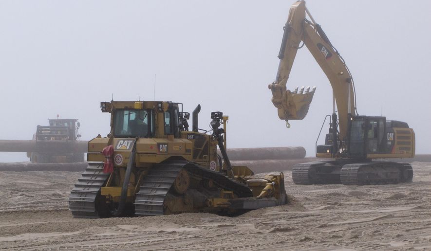 A bulldozer pushes newly pumped sand on a fog-shrouded beach in Ship Bottom, N.J. on Thursday May 7, 2015. The work is part of a $128 million project to replenish four beach towns on Long Beach Island that were seriously damaged by Superstorm Sandy in 2012.(AP Photo/Wayne Parry)