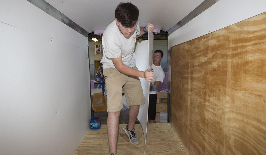 In this photo taken April 5, 2015, Colbert County High School vocational agricultural students Cody Gargis and Calvin Berryman carry sheets of paneling material inside one of the cold food storage trailers they are building at the school in Leighton, Ala., for Resource Conservation and Development councils in the state.(Matt McKean/The TimesDaily via AP) MANDATORY CREDIT