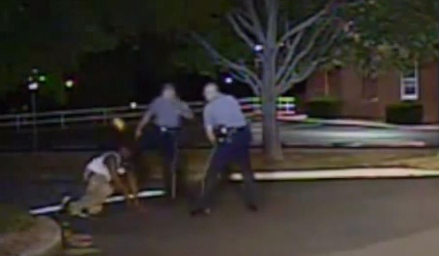 In this Aug. 24, 2013, photo made from a police dash camera video and released by the Dover Police Department, Dover Police Cpl. Thomas Webster, center, kicks Lateef Dickerson in the face as Dickerson is following orders to get on the ground during an arrest in Dover, Del. The video was released on Thursday, May 7, 2015, a week after a federal judge ruled that it was no longer considered confidential. Webster was arrested on Monday, May 4, 2015, after a grand jury indicted him for assault. (Dover Police Department via AP)