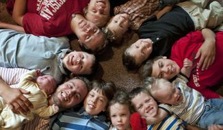 In this Aug. 6, 2013 photo,  the 12 Schwandt brothers pose for a photograph in their home Rockford, Mich.  Clockwise from bottom left, Tyler, 21, holding Tucker, 2 days,  Vinny, 10, Drew, 16, Zach, 17, Charlie, 3,  Calvin, 8, Brandon, 14, Luke, 19 mos., Gabe, 6, Wesley, 5 and Tommy, 11. The parents, Jay and Kateri Schwandt are expecting a baby on Saturday, May 9, 2015,  the day before Mother's Day, and they're sticking to their tradition of not finding out in advance whether they're having a boy or girl. (Chris Clark/The Grand Rapids Press via AP)