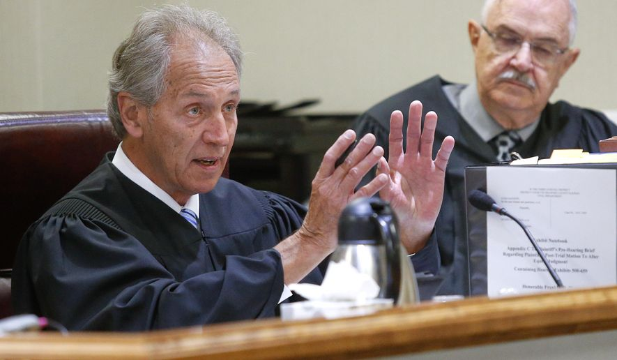 Shawnee County District Court Judge Franklin Theis, left, alongside former Sherman County District Court Judge Jack Burr, addresses the state's attorneys while listing to arguments on Thursday May 7, 2015, for the Kansas school finance case at the Shawnee County Courthouse in Topeka, Kan.  (Chris Neal/The Topeka Capital-Journal via AP)