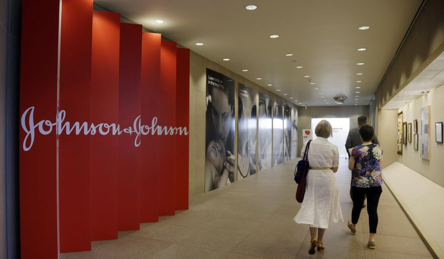 FILE - In this July 30, 2013, file photo, people walk along a corridor at the headquarters of Johnson & Johnson in New Brunswick, N.J.  Dying patients sometimes seek emergency access to experimental medicines, desperate for a last-chance treatment even if there's little proof it could help. Now drug giant Johnson & Johnson is taking an unusual step, turning to independent bioethicists for advice on when to say yes or no.(AP Photo/Mel Evans, File)