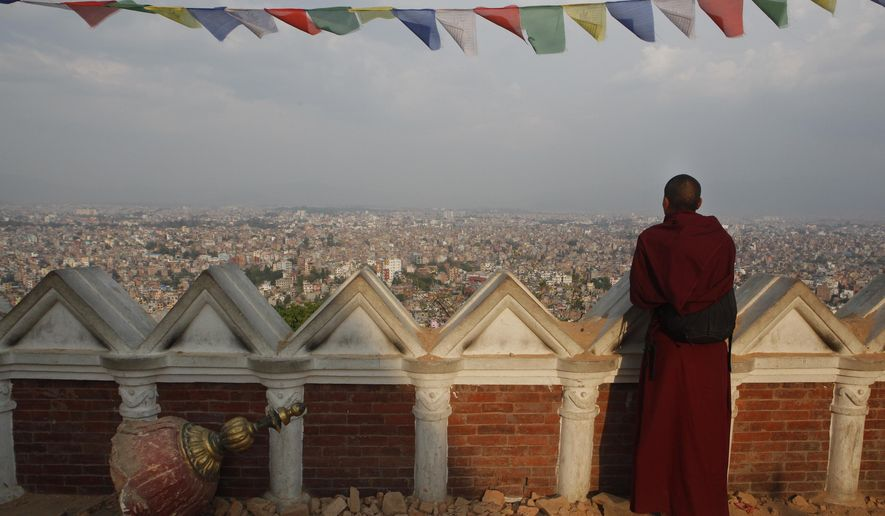 A Buddhist monk catches an aerial view of Kathmandu from the damaged Swayambhunath Stupa premises in Kathmandu, Nepal, Wednesday, May 6, 2015. The April 25 earthquake killed thousands and injured many more as it flattened mountain villages and destroyed buildings and archaeological sites in Kathmandu. (AP Photo/Niranjan Shrestha)