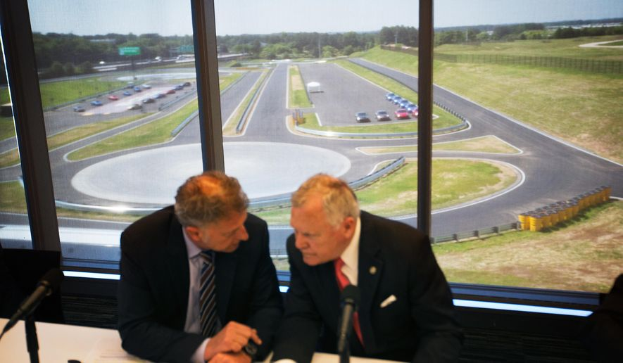 A driver development track is seen in the background as Georgia Gov. Nathan Deal, right, talks with Detlev von Platen, president and CEO of Porsche Cars North America, left, before a press conference for the opening of the company's new North American headquarters, dubbed the Porsche Experience Center, Thursday, May 7, 2015, in Atlanta. The 27-acre complex is located on the former site of a Ford Motor Co. assembly plant that was in production for almost 60 years at the edge of Hartsfield-Jackson Atlanta International Airport. It is the sports-car company's largest investment outside of Germany. (AP Photo/David Goldman)
