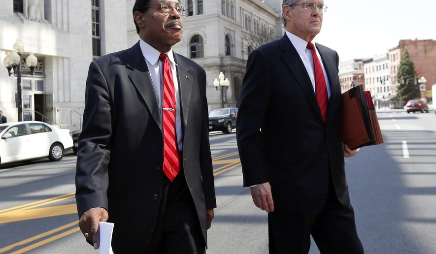 Former Assemblyman William Scarborough, D-Queens, left, leaves the federal courthouse with attorney E. Stewart Jones on Thursday, May 7, 2015, in Albany, N.Y. Scarborough is accused of submitting false expense vouchers for days he didn't actually spend in Albany.  (AP Photo/Mike Groll)