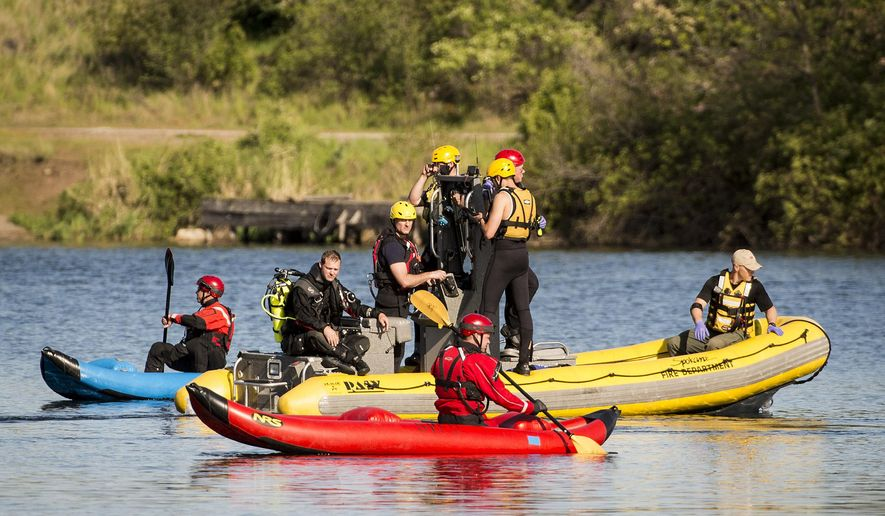 The Spokane County Sheriff's dive team and other emergency personnel search the wreckage of a small plane that crashed into the Spokane River, Thursday, May 7, 2015, near Felts Field in Spokane, Wash. (Colin Mulvany/The Spokesman-Review via AP) COEUR D'ALENE PRESS OUT
